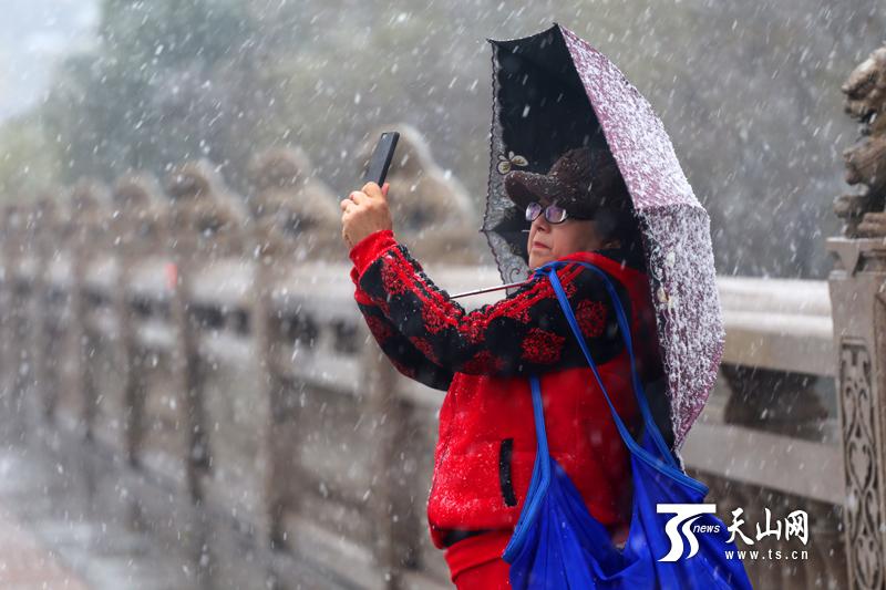 11月2日16时,在乌鲁木齐市西大桥,一位市民在雪中自拍