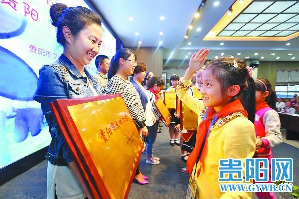 晚报小记者为获得文明校园单位的代表授牌张志红摄-2016贵阳 美作文